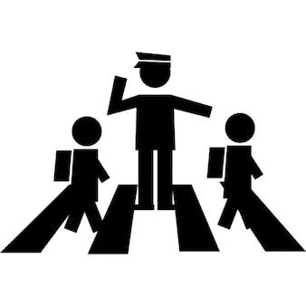 Los estudiantes que cruzan la calle con un guardia de tráfico