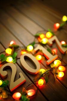 2017 Bonne année, figures en bois et lumières clignotantes sur le rétro bureau