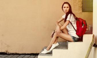 Adolescent avec sac à dos rouge assis sur les escaliers