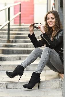 adolescent heureux tenant ses lunettes de soleil et assis sur les escaliers