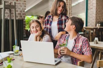 Adolescents avec un temps d'attente pour ordinateur portable au café