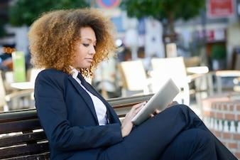 Affaires travaillant avec la tablette assis sur un banc