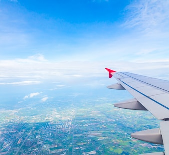 Aile d'un avion avec un arrière-plan de la ville