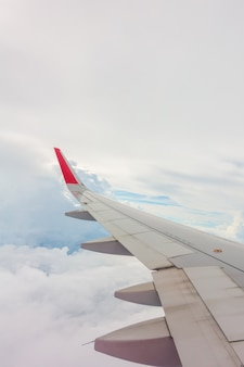 Aile d'un avion volant au-dessus des nuages.
