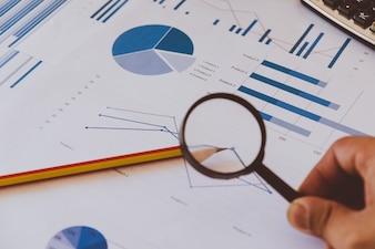 Analyse commerciale et statistiques. Rapport d'étude d'homme d'affaires utilisant une loupe.