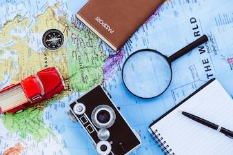 Argent, loupe, chapeau et appareil photo vintage sur fond de carte du monde. Concept de voyage.