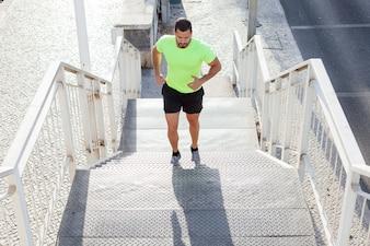 Athlète masculin concentré qui monte les escaliers