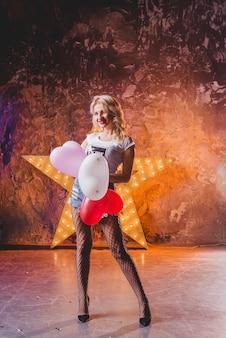 Attractive femme debout à l'étoile avec des ballons