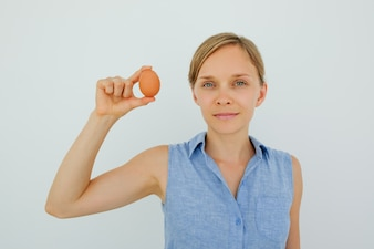 Attractive Woman Holding Egg With Two Fingers