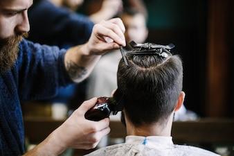 Barber coupe les cheveux de l'homme avec la tondeuse et la brosse