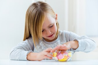 Beau enfant à manger des bonbons à la maison.