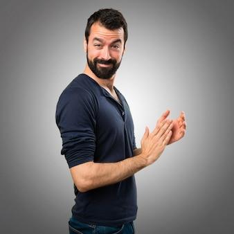 Beau homme à la barbe applaudissant sur fond gris