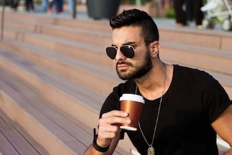 Beau jeune homme assis à l'extérieur sur les escaliers du bâtiment, tenant une tasse de café