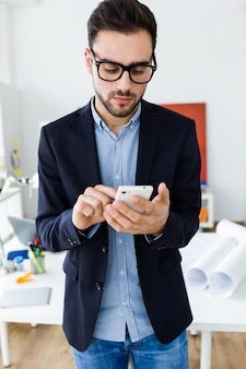 Beau jeune homme utilisant son téléphone portable au bureau.