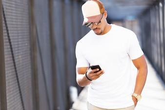 Beau jeune homme utilisant son téléphone portable dans la rue.