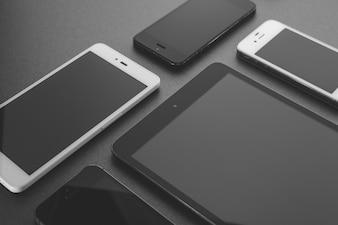 Beaucoup de téléphones intelligents différents affichés sur fond sombre, scène de bureau occupée.