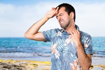 Bel homme avec une chemise à fleurs avec de la fièvre à la plage
