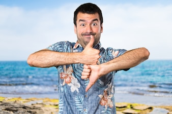 Bel homme avec une chemise à fleurs faisant un signe bon-mauvais à la plage