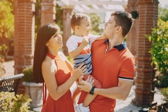 Belle famille en rouge marchant dans la rue et le parc