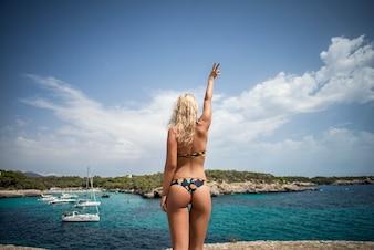 Belle femme blonde posant en bikini noir sur la falaise, profite de la mer