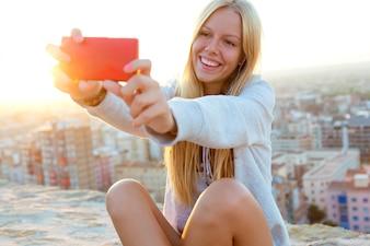 Belle fille blonde prenant une selfie sur le toit.