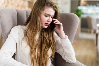 Belle fille dans un café parlant sur un téléphone portable