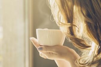 Belle fille jeune femme prend du café seul dans un café