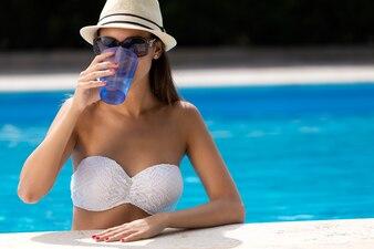 Belle fille qui boit de l'eau à la piscine.