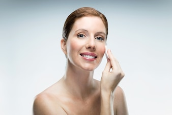 Belle jeune femme à l'aide de produits cosmétiques sur fond blanc.