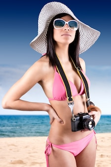 Belle jeune femme avec un bikini tenant caméra vintage rétro