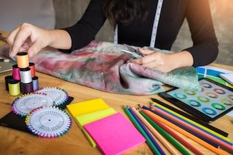 Belle jeune femme créatrice de mode choisissant un fil pour coudre des vêtements avec une machine à coudre.