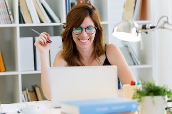 Belle jeune femme travaillant avec son ordinateur portable à la maison.