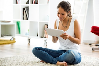 Belle jeune femme utilisant sa tablette numérique à la maison.