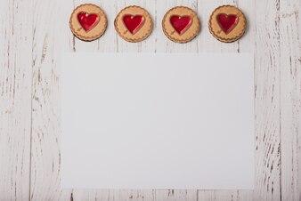 Biscuits en forme de coeur sur une table en bois avec un livre blanc