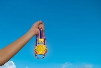 Blurred of women hands raised and holding gold medals with thailand ribbon against blue sky background pour montrer le succès dans le sport ou les entreprises, Winners succès concept.