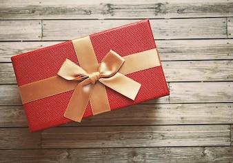 Boîte cadeau rouge avec ruban doré, effet filtre rétro