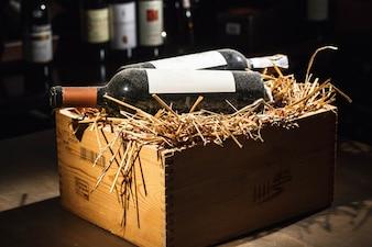 Boîte en bois avec du foin et des bouteilles de vin sur elle