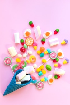 Bonbons éparpillés sur une table rose