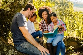 Bonne famille lisant ensemble sous un arbre