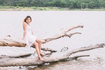 Bonne fille assise sur une bûche avec lac fond