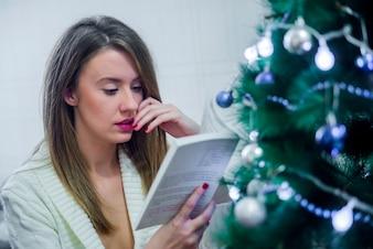 Bonne jeune femme qui livre un livre devant un arbre de Noël. Femme lisant un livre. Noël.