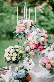 Bougies et vases avec de belles fleurs pastel