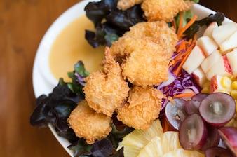 Boule de viande de crevettes frites avec sauce sucrée sur une table en bois.