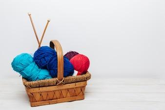 Boules de laine bleue et rouge dans le panier
