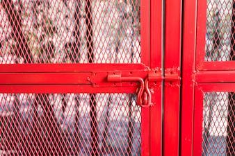 Boulon de porte rouge sur le filet de fer rouge