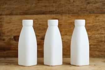 Bouteilles de lait en plastique blanc sur fond de table en bois rétro