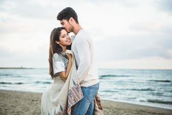 Boyfriend embrasser sa petite amie dans le front sur une plage