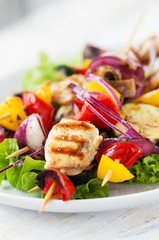 Brochettes de poulet avec des oignons sur le dessus d'une salade