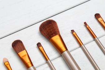 Brosses de maquillage sur un bureau en bois blanc