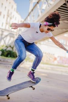Brunette girl riding skateboard making tricks